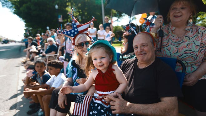 Ella Schultz, 3, of Farmington Hills waves, while she sits in her grandfather's, Bobby Berry, 62, of Dearborn; lap, while Judy Byrwa, 64, of Dearborn, left, and Kathleen Berry, 62, look on during the 90th Memorial Day parade in Dearborn, Mich. on Monday, May 26, 2014. Kimberly P. Mitchell/Detroit Free Press