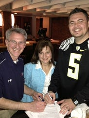 Sports Page co-owners Todd Thimesch, left, and Phil Hemming, right, pose with Angela Harrington, of the Grinnell Chamber of Commerce in 2013. The company is closing its Altoona store this summer.
