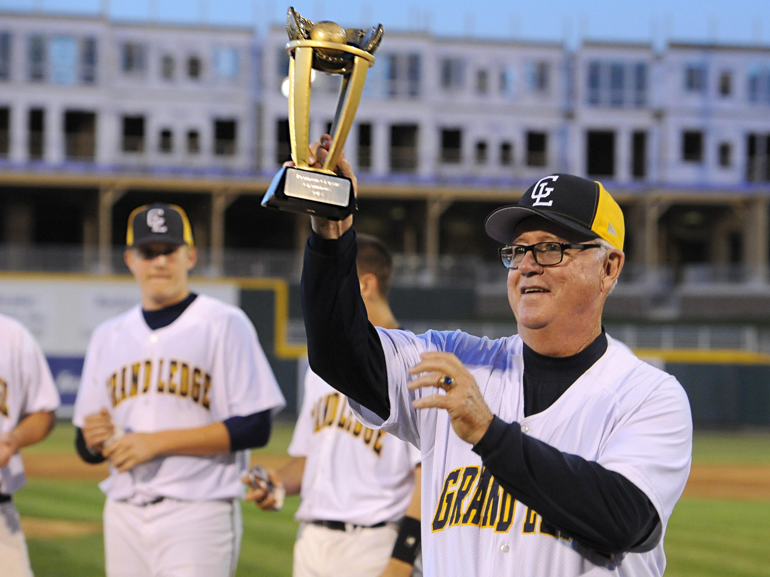 Grand Ledge head baseball coach Pat O'Keefe holds the Diamond Classic Championship trophy up to the the team's fans after the Comets' 4-1 win over St. Johns in the championship game.