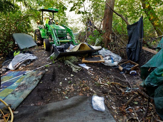 A Seattle city worker clears a large homeless encampment in the woods near Seattle's Ravenna Park neighborhood. Residents were given notice and offered shelter beds and other services, but some people in the encampment did not remove their belongings before the cleanup began.