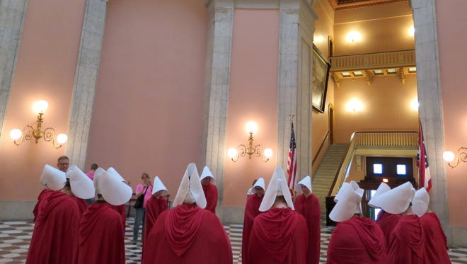 """On June 13, women dressed in character from the dystopian novel """"The Handmaid's Tale"""" stage a protest in the Ohio Statehouse Rotunda."""