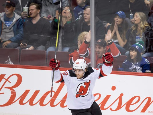 New Jersey Devils' Blake Coleman celebrates a goal by Jimmy Hayes against the Vancouver Canucks during the second period of an NHL hockey game in Vancouver, British Columbia, Wednesday, Nov. 1, 2017. (Darryl Dyck/The Canadian Press via AP)