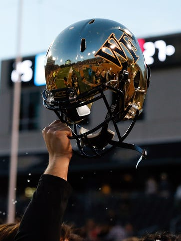 Wake Forest Demon Deacons players hold up a helmet