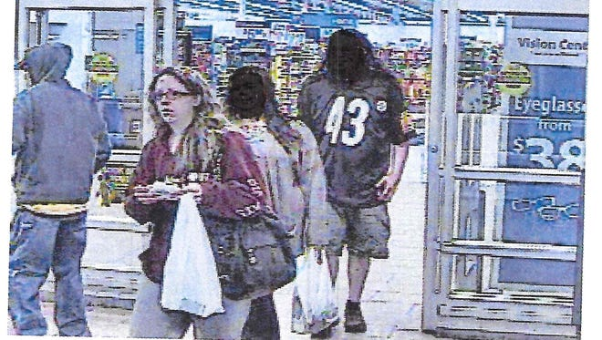 Police are seeking the identity of this woman, seen wearing glasses and carrying a white shopping bag.