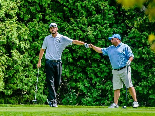 Dominic Choma, left, and his uncle Dale Choma fist bump in the13th hole tee box during the All-City Tournament final round Sunday at Forest Akers Golf Course in East Lansing. The uncle/nephew pair were 1st and 2nd beginning final round play.