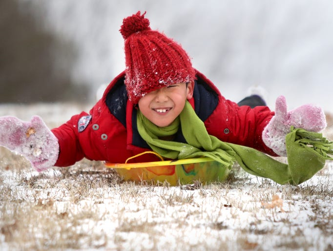 Clark Wang, 7, enjoys an adventurous head-first sled