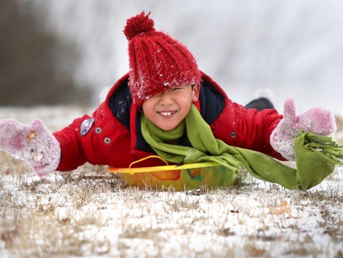 Clark Wang, 7, enjoys an adventurous head-first sled