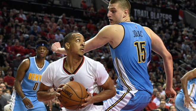 Portland Trail Blazers guard C.J. McCollum (3) looks to the basket as Denver Nuggets center Nikola Jokic (15) defends during the second half of an NBA basketball game in Portland, Ore., Wednesday, April 13, 2016. The Blazers won 107-99.