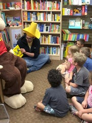 """Bookseller Adam Repash reads to a group of children at Phoenix Books Essex on May 7. The event was called """"Inspire Curiosity with Curious George."""""""