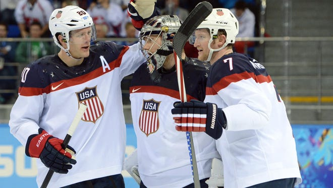 USA goalie Jonathan Quick (32) is congratulated by teammates defenseman Paul Martin (7) and defenseman Ryan Suter (20) after a win against Slovakia.