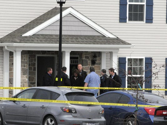 Investigators gather outside the Fox Ridge apartment where one man was killed and another critically wounded in a drug-related shooting on March 10, 2014.