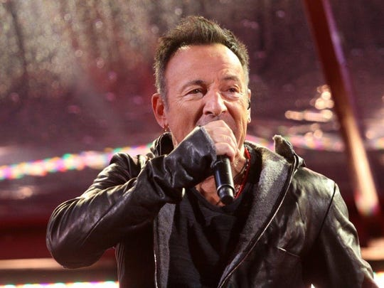 Bruce Springsteen performs with U2 in Times Square, Monday, December 1, 2014, during a World AIDS Day concert in New York, NY.