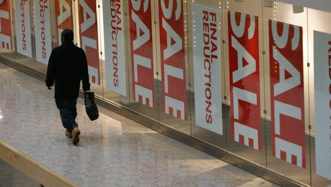 A shopper walks past store windows in Fairlane Town Center in Dearborn.