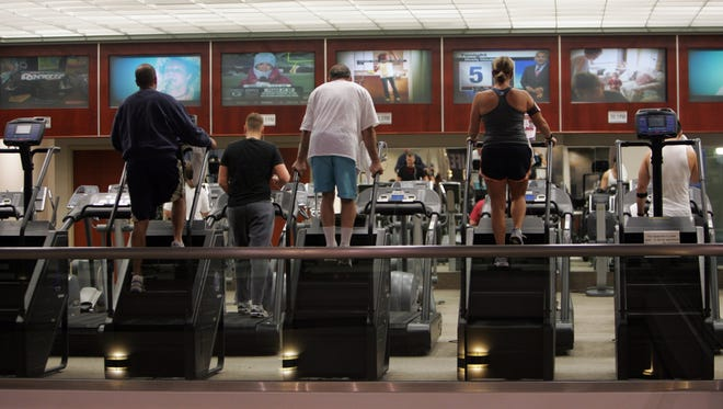 Patrons work out on steppers while watching monitor at the Lifetime Fitness in Commerce Township. Monday, December 22, 2008