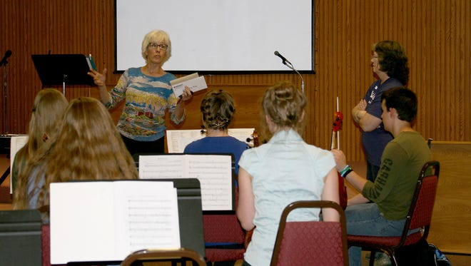 "Kathy Butler Bebout (left), the originator and first director of the SkyMeadow Youth Orchestra, was on hand at Wednesday's practice at Living Word Church in Yellville. Orchestra members gave her ""thank-you gifts"" for her time as director. The SkyMeadow Youth Orchestra, under the direction of Robin Thomis (right), will perform at 6:30 p.m. Tuesday, May 22, at Dunbar Auditorium. The performance is free, but donations will be accepted."