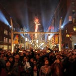 Fans watch the fireworks as they wait to see Darius Rucker and his band perform at the Super Bowl Village in 2012.