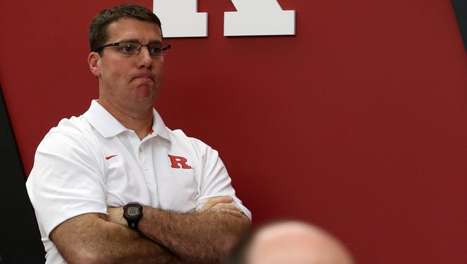 Rutgers coach Chris Ash (top) peers on from the team meeting room over the shoulder of defensive coordinator Jay Niemann.