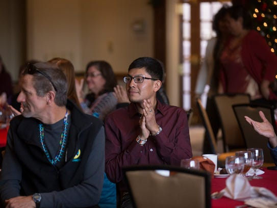 Rygie Bekay, center, of Navajo Yes, applauds after his group received a grant from NTEC's Community Benefit Fund Thursday during an awards ceremony at the Courtyard by Marriott in Farmington.
