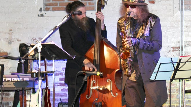 Don Bailey, right, on saxaphone and Brandon Patterson on bass entertain during Masked Crusaders of UAFS Halloween costume fundraiser benefiting Antioch for Youth and Families at The Bakery District on Oct. 24.