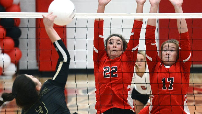 Mansfield's Brooke Wright, from right, and Brooklyn Adams attempt to block the shot by Charleston's Julianna Arroyo during the first set on Monday, Oct. 5 in Mansfield. Mansfield won the match 3-1.