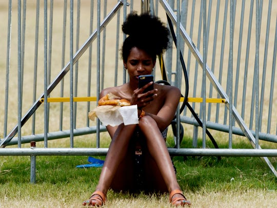 A fest-goer uses their cell phone at Bonnaroo Music