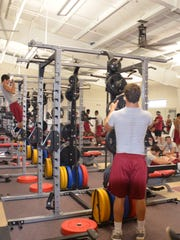 Members of the Pineville football team work out in the school's new weight room on Tuesday.