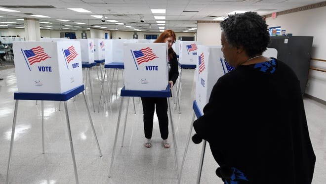 Linda Moreno (back) and Leisha Bean Clark set up voting booths at the Ezell Hester Community Center in Boynton Beach so that early voting can take place in the 2020 Presidential Preference Primary. Saturday, March 7, 2020.