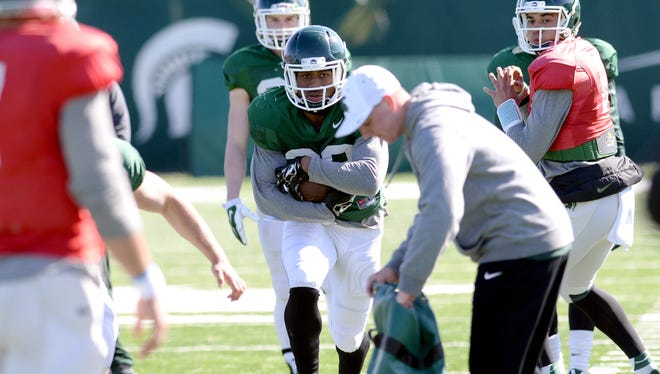 Michigan State running back Madre London takes a handoff during a drill April 6, 2016, in East Lansing.