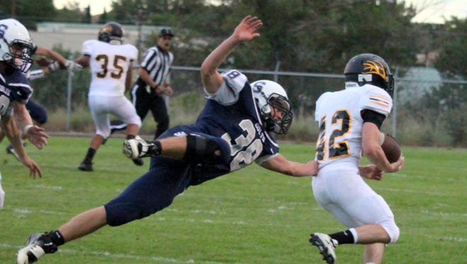 Silver High's Chance Porter dives to hang on to a Round Valley running back during Friday night's football opener. Porter also scored the only touchdown for the Colts in the loss.