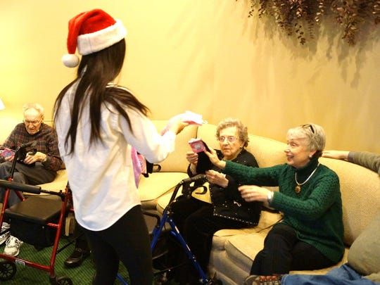 The Little Stars director Anna Sun (11th grader) distributes fuzzy socks at Halsted Place Senior Residences.