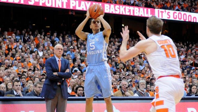 North Carolina Tar Heels guard Marcus Paige (5) takes a jump shot as Syracuse Orange head coach Jim Boeheim looks on.