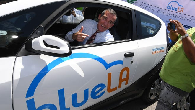 Los Angeles Mayor Eric Garcetti tries out a car at the launch of what is being billed as the nation's largest electric vehicle' car sharing program for disadvantaged communities