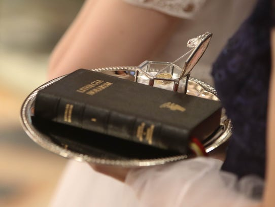A veil, ring and prayer book were given during Mass