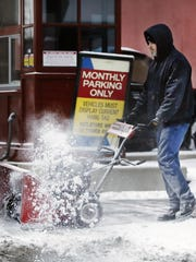 Snow was removed from a Downtown Indianapolis sidewalk on Wednesday, Jan. 20, 2016.