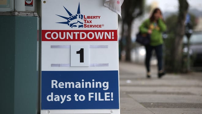 A sign advertising one day remaining before the tax filing deadline is posted in front of  Liberty Tax Service.