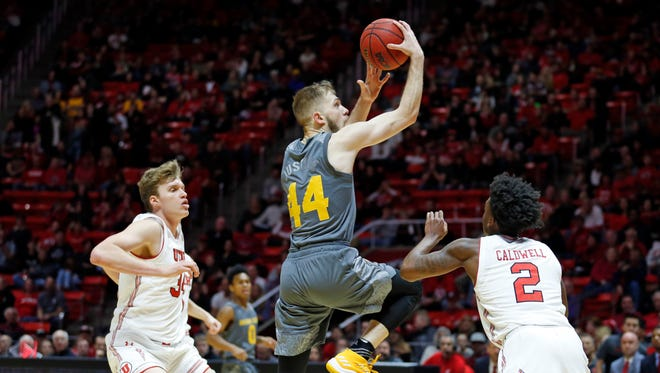 Arizona State guard Kodi Justice (44) goes to the basket as Utah's Jayce Johnson, left, and Kolbe Caldwell (2) defend in the first half of an NCAA college basketball game Sunday, Jan. 7, 2018, in Salt Lake City.