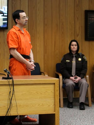Larry Nassar stands to hear an Eaton County (Mich.) Circuit judge deliver his sentence Monday, Feb. 5, 2018, the third and final day of sentencing in Charlotte, Mich.