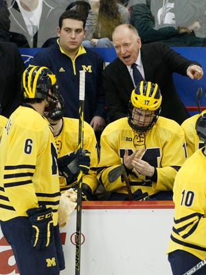Michigan hockey coach Red Berenson, top right, gestures while giving instructions to his players Dec. 29, 2014.