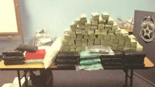 Authorities show drugs, guns and cash netted during an investigation.