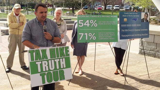 UNC Asheville student Austin Hanna speaks at a press conference Friday in Pack Square Park on the effects of state tax and fee changes.