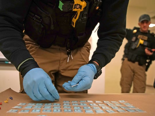 An officer with the New Castle County Police department's MET (Mobile Enforcement Team) starts counting out five bundles of heroin marked Jaguar taken from a suspected dealer during a traffic violation stop on North Broom Street near Lancaster Pike in 2016.