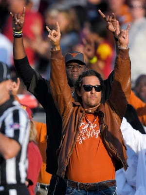 Actor Matthew McConaughey, right, and former Texas quarterback Vince Young gesture as the Texas team runs out onto the field prior to an NCAA college football game between Southern California and Texas on in Los Angeles.