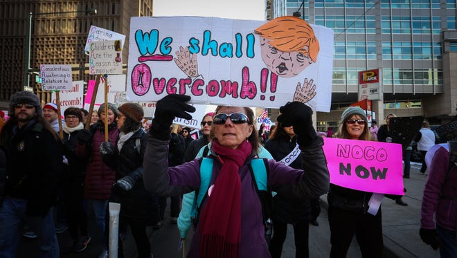 Karen Schooler, a Colorado Springs resident, holds a sign against President Donald Trump as she marches through downtown Denver as a part of the Women's March on Colorado.