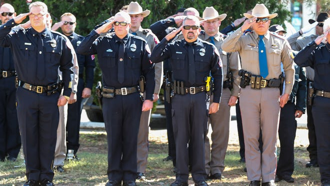 Officers salute as Sgt. Freddy Dietz Jr. casket is carried to the gravesite Thursday, Nov. 9, 2017, at Belvedere Cemetery.
