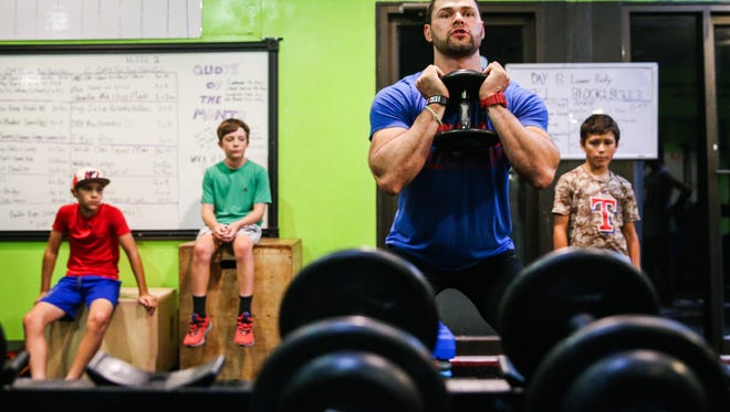 Matt Cutrer demonstrates an exercise during a youth training camp Wednesday, July 18, 2018, at Fitness United.