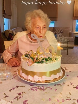 Lucille Ferruzzi blows out the candle on her 100th birthday cake at the Village at Proprietors Green in Marshfield.  Family Photo