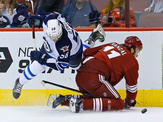 Winnipeg Jets center Eric O'Dell (58) collides with Phoenix Coyotes center Martin Hanzal (11) during the first period of their NHL game Tuesday, April 1, 2014 in Glendale, Ariz.