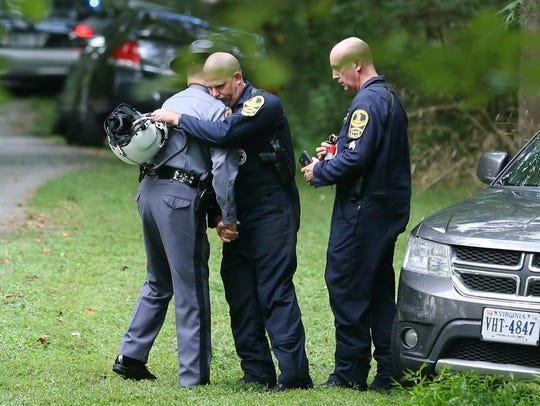 Authorities embrace while working near the scene of