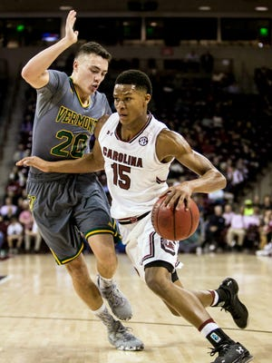 South Carolina guard PJ Dozier (15) drives around Vermont guard Ernie Duncan (20) in the first half.