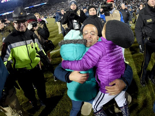 Penn State head coach James Franklin is embraced by his daughters after the Nittany Lions defeated Michigan State 45-12 to win the Big 10 East Championship in State College on Nov. 26, 2016.